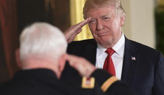 President Donald Trump, right, salutes retired Army Capt. Gary M. Rose, left, before bestowing him with the nation's highest military honor, the Medal of Honor, during a ceremony in the East Room of the White House in Washington, Monday, Oct. 23, 2017. (AP Photo/Susan Walsh)