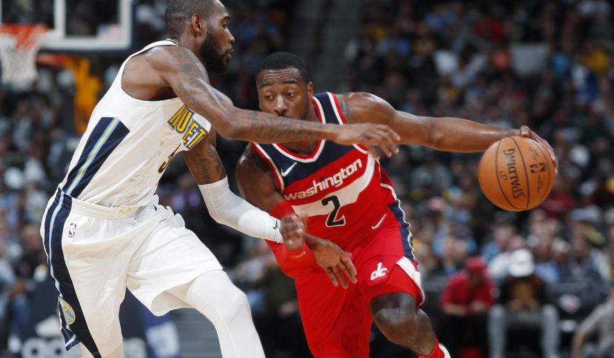 Denver Nuggets guard Will Barton, left, blocks Washington Wizards guard John Wall as he drives the lane to the rim in the first half of an NBA basketball game, Monday, Oct. 23, 2017, in Denver. (AP Photo/David Zalubowski)
