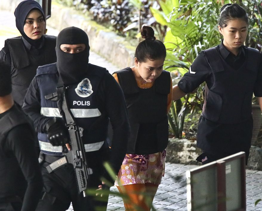 Indonesian Siti Aisyah, second from right, is escorted by police as she arrives for a court hearing at Shah Alam court house in Shah Alam, outside Kuala Lumpur, Malaysia, Wednesday, Oct. 25, 2017. Aisyah and Vietnamese Doan Thi Huong were accused of killing Kim Jong-nam, the half brother of North Korean leader Kim Jong-un, at a Malaysian airport. (AP Photo/Sadiq Asyraf)