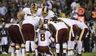 Washington Redskins quarterback Kirk Cousins huddles with teammates during an NFL football game against the Philadelphia Eagles, Monday, Oct. 23, 2017, in Philadelphia. (AP Photo/Matt Rourke)