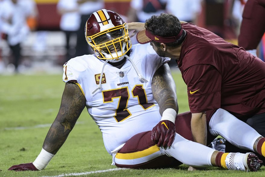 FILE - In this Oct. 2, 2017, file photo, Washington Redskins offensive tackle Trent Williams (71) is treated during the first half of an NFL football game in Kansas City, Mo. Williams continues to play through a knee injury that will likely require surgery at some point (AP Photo/Reed Hoffmann, File) **FILE**