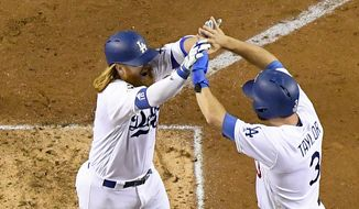 Los Angeles Dodgers' Justin Turner, left, celebrates his two-run home run with Chris Taylor against the Houston Astros during the sixth inning of Game 1 of baseball's World Series Tuesday, Oct. 24, 2017, in Los Angeles. (AP Photo/Mark J. Terrill)