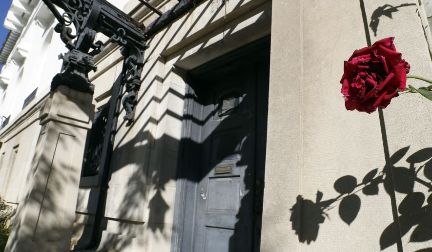 In this Oct. 19, 2017 photo, a rose blooms in front of the vacant Serbian embassy in Washington. Washington residents and politicians are up in arms about an only-in-DC phenomenon: a string of former embassies and diplomatic buildings whose governments have essentially abandoned them. (AP Photo/Alex Brandon)