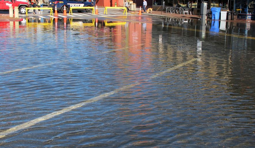 """Police close Dock Street in downtown Annapolis, Md., on Tuesday, Oct. 24, 2017, after winds at high tide caused flooding on two streets in Maryland's capital city. Rhonda Wardlaw, a spokeswoman for the city, said the 10- to 15-mile-per-hour winds created """"above an average nuisance flood."""" (AP Photo/Brian Witte)"""