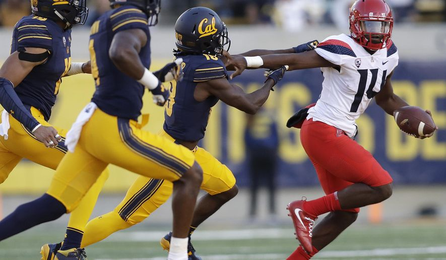 FILE - In this Oct. 21, 2017, file photo, Arizona quarterback Khalil Tate, right, stiff-arms California cornerback Marloshawn Franklin Jr., second from right, during the first half of an NCAA college football game in Berkeley, Calif. An injury to Brandon Dawkins three games ago gave Tate a chance and he has simply been one of the best players in the country since. In the last three games Tate has run for 694 yards and passed 468 while accounting for 11 touchdowns.(AP Photo/Marcio Jose Sanchez, File)
