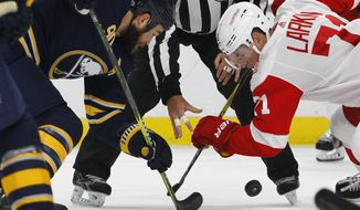 Buffalo Sabres Ryan O'Reilly (90) and Detroit Red Wings Dylan Larkin (71) take the face-off during the first period of an NHL hockey game, Tuesday Oct. 24, 2017, in Buffalo, N.Y. (AP Photo/Jeffrey T. Barnes)