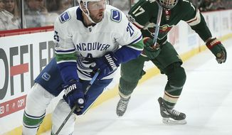 Vancouver Canucks' Thomas Vanek (26) controls the puck in front of Minnesota Wild's Marcus Foligno (17) in the second period of an NHL hockey game Tuesday, Oct. 24, 2017, in St. Paul, Minn. (AP Photo/Stacy Bengs)