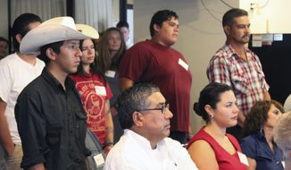 FILE - In this Sept. 30, 2015, file photo, a group of young farmers and ranchers stand up as advocates speak about discrimination and civil rights violations involving Latinos and women during a news conference in Albuquerque, N.M. A federal judge has dismissed claims by Hispanic ranchers along the New Mexico-Colorado border who allege the U.S. Forest Service ignored the social and economic consequences of limiting grazing on land that had been used by their families for centuries. The ranchers say they are disappointed, since they saw the case as a way to validate concerns about discrimination and civil rights violations that have been documented over the years. (AP Photo/Susan Montoya Bryan, File)