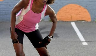 In a Sept. 21, 2017 photo, Yasmin Mullings stretches in the parking lot of the Running Room in St. Paul, Minn. before a training run. Mullings, a Ramsey County prosecutor, lost consciousness in a courtroom last year while grilling a key defendant in a complex, high profile sex-trafficking case. A month later she learned that a rare infection in her heart had caused the organ to fail and she had a heart transplant. Mullings ran a 10-mile race during Medtronic's Twin Cities marathon weekend on Oct. 1. (Ginger Pinson/Pioneer Press via AP)