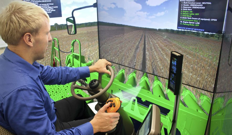 "In this Tuesday, Oct. 17, 2017 photo, Nick Schiltz, Agricultural Sciences instructor at Riverland Community College, demonstrates how he uses the new combine simulator for training students on operating farm equipment at the community college in Austin, Minn. ""This is very similar, or very close to the real thing,"" Schiltz said while using the simulator. ""We have some tremendous training opportunity here (for students)."" (Hannah Yang/The Rochester Post-Bulletin via AP)"