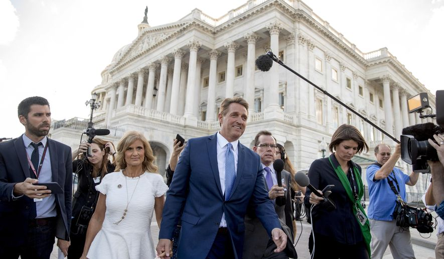 Sen. Jeff Flake, R-Ariz., accompanied by his wife Cheryl, leaves the Capitol in Washington, Tuesday, Oct. 24, 2017, after announcing he won't seek re-election in 2018. (AP Photo/Andrew Harnik)