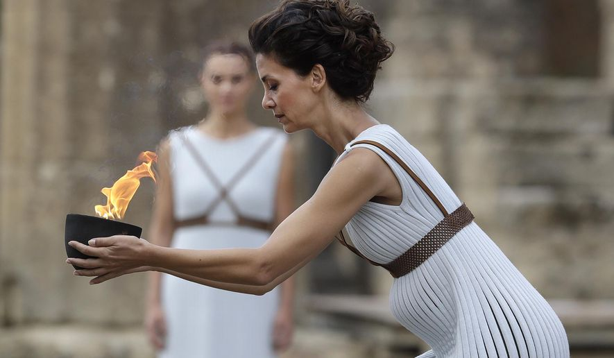 Actress Katerina Lehou as high priestess, carries a bowl of fire during the lighting ceremony of the Olympic flame in Ancient Olympia, southwestern Greece, on Tuesday, Oct. 24, 2017. The flame will be transported by torch relay to Pyeongchang, South Korea, which will host the Feb. 9-25, 2018 Winter Olympics. (AP Photo/Thanassis Stavrakis)