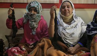 In this Sept 18, 2017 photo, Tasleema Bilal , right, and her teenage niece Kousain Ajaz, show their chopped braids inside their home in Srinagar, India.  Unidentified assailants have chopped off long-braided hair of over 100 mostly teenage girls and young women since last month in Indian-controlled Kashmir. The attacks have intensified fear and panic, protests and even vigilantes in the disputed Himalayan region, where most population is already exhausted and traumatized by decades of brutal conflict. (AP Photo/Mukhtar Khan)