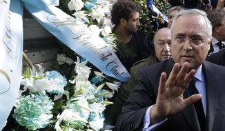 Lazio soccer team president Claudio Lotito gives a statement to the press after laying a wreath outside Rome's Synagogue, Tuesday, Oct. 24, 2017. Lazio fans have a long history of racism and anti-Semitism and the Roman club's supporters established another low over the weekend when they littered the Stadio Olimpico with superimposed images of Anne Frank _ the young diarist who died in the Holocaust _ wearing a jersey of city rival Roma. In the background left is Lazio player Felipe Anderson. (AP Photo/Gregorio Borgia)