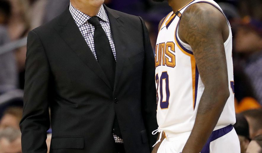 Phoenix Suns head coach Jay Triano speaks with Phoenix Suns guard Troy Daniels (30) during the first half of an NBA basketball game against the Sacramento Kings, Monday, Oct. 23, 2017, in Phoenix. It was Triano's first game as the Suns' head coach. (AP Photo/Matt York)