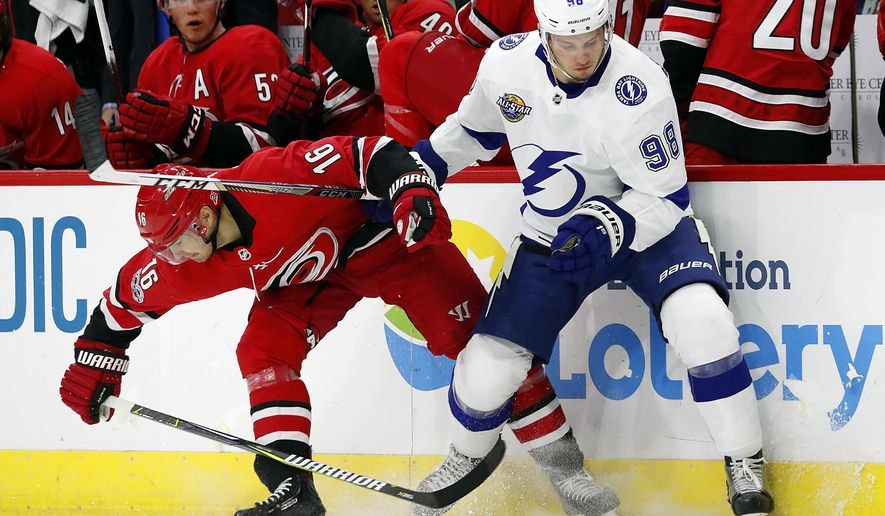Carolina Hurricanes' Marcus Kruger (16) collides with Tampa Bay Lightning's Mikhail Sergachev (98) during the first period of an NHL hockey game, Tuesday, Oct. 24, 2017, in Raleigh, N.C. (AP Photo/Karl B DeBlaker)