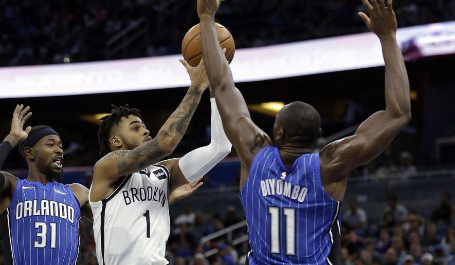 Brooklyn Nets' D'Angelo Russell (1) gets between Orlando Magic's Terrence Ross (31) and Bismack Biyombo (11) for a shot during the first half of an NBA basketball game, Tuesday, Oct. 24, 2017, in Orlando, Fla. (AP Photo/John Raoux)