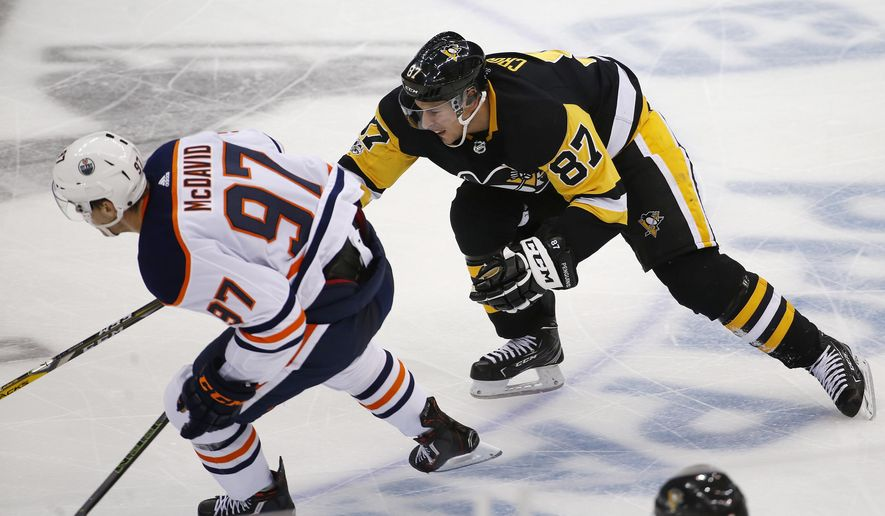 Pittsburgh Penguins' Sidney Crosby (87) tries to slow down Edmonton Oilers' Connor McDavid (97) in the third period of an NHL hockey game in Pittsburgh, Tuesday, Oct. 24, 2017. The Penguins won 2-1 in overtime. (AP Photo/Gene J. Puskar)