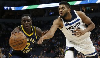 Indiana Pacers' Darren Collison, left, beats Minnesota Timberwolves' Karl-Anthony Towns to the loose ball during the first half of an NBA basketball game Tuesday, Oct. 24, 2017, in Minneapolis. (AP Photo/Jim Mone)