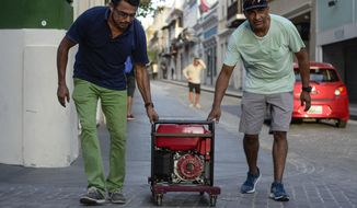 In this Friday, Oct. 20, 2017 photo, men push a generator along Fortaleza street, one month after Hurricane Maria in San Juan, Puerto Rico. Maria roared across the island on Sept. 20 and after a month, only 30 percent of residents have power. (AP Photo/Carlos Giusti)
