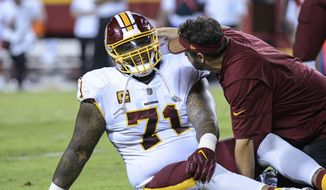 FILE - In this Oct. 2, 2017, file photo, Washington Redskins offensive tackle Trent Williams (71) is treated during the first half of an NFL football game in Kansas City, Mo. Williams continues to play through a knee injury that will likely require surgery at some point (AP Photo/Reed Hoffmann, File)