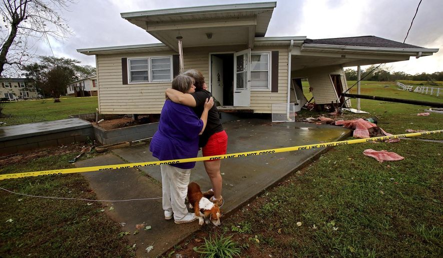 JoAnn Perez, right, hugs friend Melissa Porter in front of her damaged home in Shelby, N.C., Monday, Oct. 23, 2017. Perez arrived home shortly after Monday's storms to see her home pushed away from its foundation. Her two dogs and cats were the only occupants when the storm hit. All three pets were uninjured. (Brittany Randolph/The Star via AP)