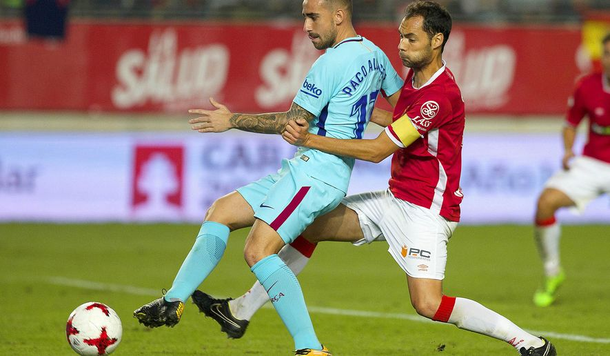 Barcelona's Paco Alcacer, left, vies for the ball with Murcia's Alex Ortiz during the Copa del Rey round of 16 first leg soccer match between Murcia and Barcelona at the Nueva Condomina stadium in Murcia, Tuesday, Oct. 24, 2017. Barcelona won 3-0. (AP Photo/Ferran Viros)