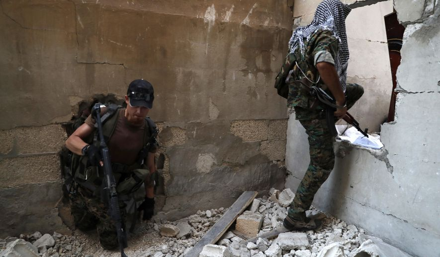 FILE - In this July 27, 2017 file photo, U.S.-backed Syrian Democratic Forces fighters, pass through holes as they cross from building to building to hide from snipers, on the front line with Islamic State group militants, in Raqqa, Syria. As U.S.-allied fighters hurtle down the eastern banks of the Euphrates River, a showdown could ensue between the U.S. and Russia, whose allies are racing to take over the same strategic oil-rich territory from IS. (AP Photo/Hussein Malla, File)
