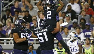 FILE - In this Saturday, Oct. 21, 2017, file photo, TCU wide receiver Taj Williams (2) and teammates Austin Schlottmann (51) and Joseph Noteboom (68) celebrate Williams' touchdown catch as Kansas cornerback Kyle Mayberry (16) looks away during the second half of an NCAA college football game in Fort Worth, Texas. Fourth-ranked TCU is the Big 12's only undefeated team going into the last game before the initial College Football Playoff rankings of the 2017 season.  (AP Photo/Ron Jenkins, File)