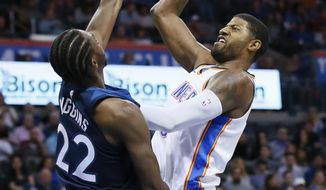Oklahoma City Thunder forward Paul George, right, shoots over Minnesota Timberwolves guard Andrew Wiggins (22) in the third quarter of an NBA basketball game in Oklahoma City, Sunday, Oct. 22, 2017. Minnesota won 115-113. (AP Photo/Sue Ogrocki)