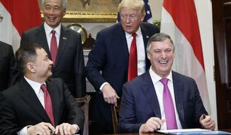 President Donald Trump and Singapore's Prime Minister Lee Hsien Loong look on as Singapore Airlines CEO Goh Choon Phong, left, and Kevin McAllister, president and chief executive officer of Boeing Commercial Airplanes, sign a contract in the Roosevelt Room of the White House, Monday, Oct. 23, 2017, in Washington. (AP Photo/Evan Vucci)
