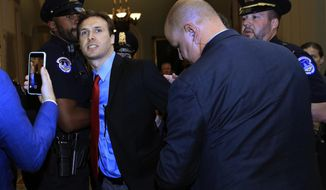 """A protester is detained after throwing Russian flags with the word """"Trump"""" printed on it toward President Donald Trump as he arrived at the U.S. Capitol in Washington, Tuesday, Oct. 24, 2017, for a lunch with Republican senators. (AP Photo/Manuel Balce Ceneta)"""