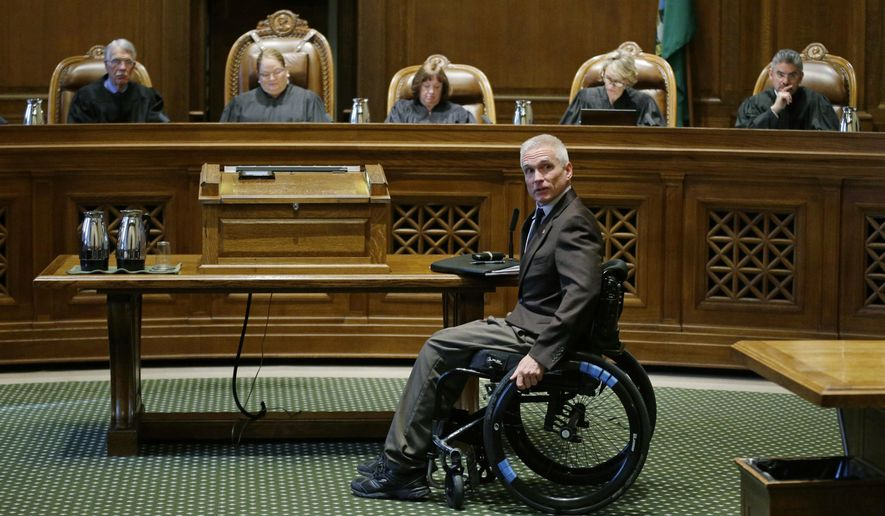 Tom Ahearne, the lead attorney in a lawsuit against the state of Washington regarding the funding of education, moves away from a table after speaking Tuesday, Oct. 24, 2017, during a Washington Supreme Court hearing in Olympia, Wash. The hearing was held to determine if Washington state has complied with a court mandate to fully fund the state's basic education system. (AP Photo/Ted S. Warren)