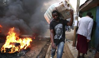 A Kenyan man carried his belongings through Nairobi's slums after supporters of the National Super Alliance burned tires to block roads Wednesday before voters go to the polls. (Associated Press)