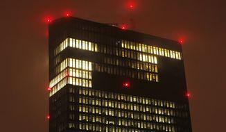 The lights in the offices of the European Central Bank shine in Frankfurt, Germany, early Wednesday, Oct. 25, 2017. The governing council of the ECB will meet on Thursday.(AP Photo/Michael Probst)
