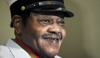 """In this Dec. 20, 2013, file photo, legendary musician Fats Domino is named """"Honorary Grand Marshall"""" of the Krewe of Orpheus, the star-studded Carnival club that traditionally parades the night before Mardi Gras in New Orleans. Domino, the amiable rock 'n' roll pioneer whose steady, pounding piano and easy baritone helped change popular music even as it honored the grand, good-humored tradition of the Crescent City, has died. He was 89. Mark Bone, chief investigator with the Jefferson Parish, Louisiana, coroner's office, said Domino died Tuesday, Oct. 24, 2017. (AP Photo/Doug Parker, File)"""