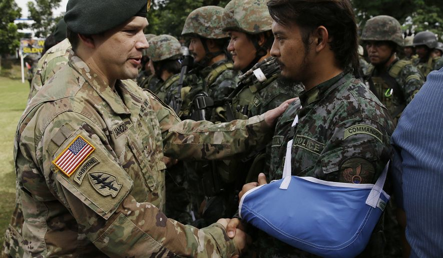 A member of the U.S. Army who trains Philippine troopers welcomes a wounded Philippine National Police Special Action Force who just got back from Marawi, southern Philippines, as they arrive at Camp Bagong Diwa, south of Manila, Philippines on Wednesday, Oct. 25, 2017. The Islamic State group sent at least $1.5 million to finance the recently ended siege of the southern Philippine city of Marawi, with the assault leaders using the 2014 IS seizure of the Iraqi city of Mosul as a blueprint, the Philippine military chief recently said. (AP Photo/Aaron Favila)