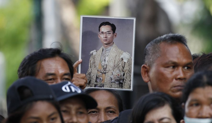 A Thai mourner holds up the portrait of the late King Bhumibol Adulyadej near Grand Palace to take part in the Royal Cremation ceremony in Bangkok, Thailand, Wednesday, Oct. 25, 2017. Thailand on Wednesday began an elaborate five-day funeral for King Bhumibol with his son, the new monarch, performing Buddhist merit-making rites in preparation for moving Bhumibol's remains to a spectacular golden crematorium. (AP Photo/Sakchai Lalit)