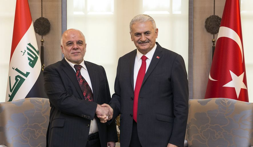 Turkey's Prime Minister Binali Yildirim, right, and Iraqi Prime Minister Haider al- Abadi shake hands during a welcome ceremony in Ankara, Turkey, Wednesday, Oct. 25, 2017. (Pool photo via AP)