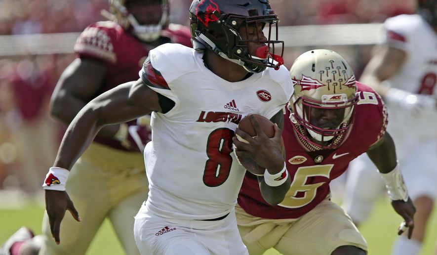 FILE - In this Saturday, Oct. 21, 2017, file photo, Louisville's Lamar Jackson gets past Florida State's Matthew Thomas to score in the first quarter of an NCAA college football game in Tallahassee Fla. The ACC's two leading rushers as November nears are quarterbacks: Louisville's Lamar Jackson and Georgia Tech's Taquon Marshall. If it holds up, it'll be the first time in conference history the leading rusher wasn't a running back. (AP Photo/Steve Cannon, File)