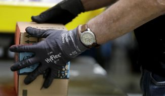 FILE - In this Tuesday, Aug. 1, 2017, file photo, an employee packages a product at the Amazon Fulfillment center in Robbinsville Township, N.J. On Wednesday, Oct. 25, 2017, Amazon said that it will launch a new service in November that will let delivery people inside homes to drop off packages. (AP Photo/Julio Cortez, File)