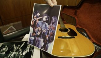 In this photo made Friday, Oct. 13, 2017, Garry Shrum, a music memorabilia specialist at Heritage Auctions, holds a photo of that displays an acoustic guitar that belonged to Bob Dylan in Dallas. Heritage Auctions said the 1963 Martin D-28 acoustic guitar will be offered up Nov. 11 in Dallas. (AP Photo/LM Otero)