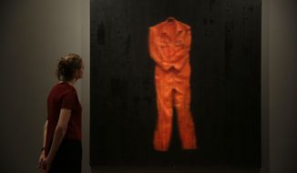 """A staff member poses for photographs by looking at British artist John Keane's painting """"Bound"""" during the media preview for the """"Age of Terror: Art since 9/11"""" exhibition at the Imperial War Museum in London, Wednesday, Oct. 25, 2017. The exhibition, which runs from Oct. 26 until May 28, 2018, considers artists' responses to war and conflict since the attacks of Sept. 11, 2001. (AP Photo/Matt Dunham)"""