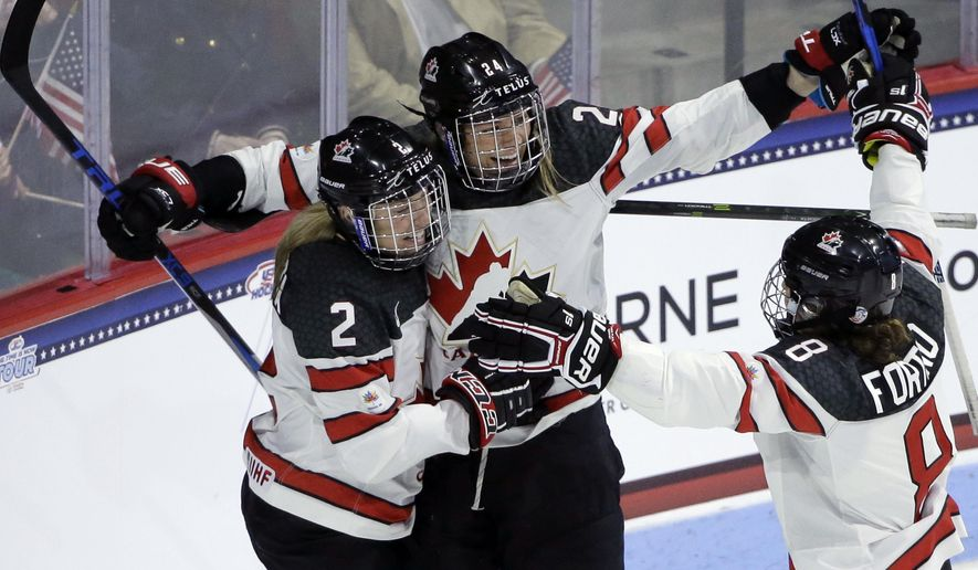 Canada's Natalie Spooner, center, celebrates with teammates Meghan Agosta, left, and Laura Fortino, right, after scoring during the first period of a women's hockey game, Wednesday, Oct. 25, 2017, in Boston. (AP Photo/Steven Senne)