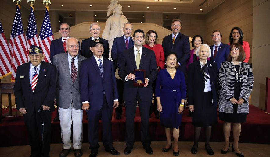 Speaker of the House Paul Ryan of Wis., presents the Congressional Gold Medal to Filipino veterans of World War II and their next of kin, from left, Celestino Almeda, Frank Francone, Aquilino Delen, Ryan, Alicia Benitez, Margrit Baltazar and Caroline Burkhart, during a ceremony at the Emancipation Hall on Capitol Hill in Washington, Wednesday, Oct. 25, 2017. Standing with the recipients are, from left back row, Veterans Affairs Secretary David Shulkin, Senate Majority Leader Mitch McConnell of Ky., Senate Minority Leader Chuck Schumer of New York, House Minority Leader Nancy Pelosi of Calif., Sen. Dean Heller, R-Nev., Sen. Mazie Hirono, D-Hi., Rep. Ed Royce, R-Calif., and Rep. Tulsi Gabbard, D-Hi. (AP Photo/Manuel Balce Ceneta)