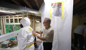 In this July 12, 2017, file photo, George Riegel, Jr., M.D., right, owner of Asbestos Removal Technologies Inc., helps prepare a personal air monitor on job forman Megan Eberhart before asbestos abatement in Howell, Mich. Congress ordered the EPA review last year to gauge risks of asbestos and nine other highly toxic substances and find better ways to manage them for public safety. (AP Photo/Paul Sancya)