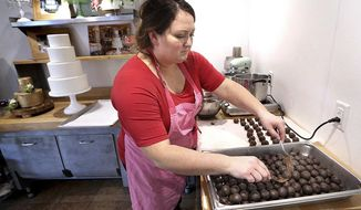 In a Thursday, Oct. 19, 2017 photo, Jennifer Barney, owner of Meringue Bakery, dips cake pieces into chocolate to make cake truffles at her commercial kitchen at her home in rural Stoddard, Wis. Barney was chosen to be a contestant on the Food Network's Holiday Baking Championship which starts airing Monday, Nov. 6. (Peter Thomson/La Crosse Tribune via AP)