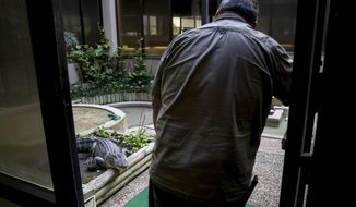 "In this Aug. 18, 2017 photo, Troy Stuart, a maintenance worker at First National Bank of Alvin, talks to ""Lucy,"" one of two alligators that live in the atrium of the bank in Alvin, Texas.  The First Bank of Alvin has been home to alligators for nearly half a century. Stuart likened the alligators to puppies. ""I get the same excitement a little kid gets on Christmas,"" he said. ( Jon Shapley /Houston Chronicle via AP)"