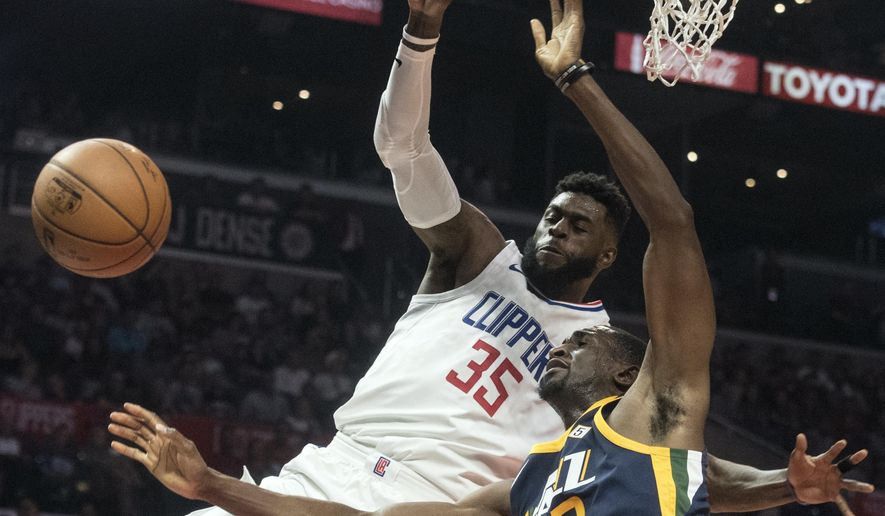 Los Angeles Clippers center Willie Reed, left, fouls Utah Jazz forward Ekpe Udoh during the first half of an NBA basketball game Tuesday, Oct. 24, 2017, in Los Angeles. (AP Photo/Kyusung Gong)
