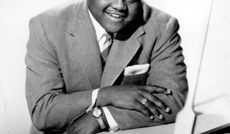 FILE - This 1956 file photo shows singer, composer and pianist Fats Domino.  The amiable rock 'n' roll pioneer whose steady, pounding piano and easy baritone helped change popular music even as it honored the grand, good-humored tradition of the Crescent City, has died. He was 89. Mark Bone, chief investigator with the Jefferson Parish, Louisiana, coroner's office, said Domino died Tuesday, Oct. 24, 2017.  (AP Photo, File)